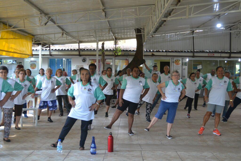 Foto dos alunos do projeto Viver Melhor praticando atividade física, todos eles utilizam o uniforme do projeto, uma camiseta branca com as mangas verdes. O ambiente é um galpão coberto, com bastante claridade entrando.